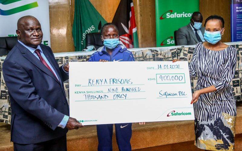 Safaricom PLC Sponsorship Manager Peris Nduta Muhoro (right) presents a dummy cheque worth KES 900,000 to World Cross Country Bronze Medallist Lilian Kasait (centre) and Commissioner General Prison Service Wycliffe O. Ogallo at Magereza House.